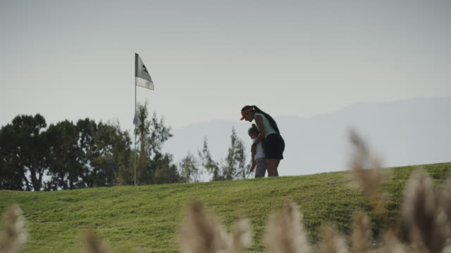 slow motion of distant woman positioning golfing girl / cedar hills, utah, united states - golf stock videos & royalty-free footage
