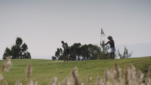 vidéos et rushes de slow motion of distant women golfing and high-fiving / cedar hills, utah, united states - golf