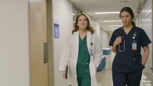 slow motion of doctor and nurse walking and talking in hospital corridor / salt lake city, utah, united states - nurse walking stock videos & royalty-free footage