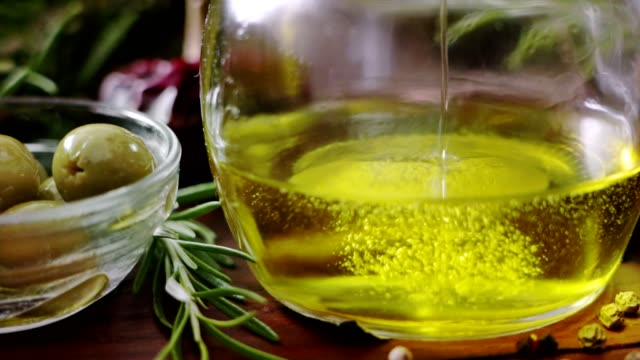 slow motion of dolly shot of pouring olive oil into bottle in rustic kitchen with olives in pan - olive oil stock videos & royalty-free footage
