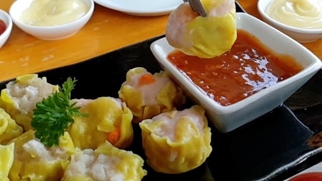 vídeos de stock e filmes b-roll de slow motion of dumpling on sauce. - invertebrado