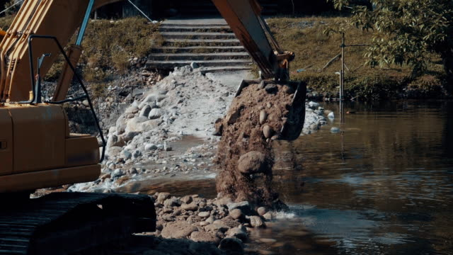 slow motion of excavator working in a river - vehicle scoop stock videos and b-roll footage