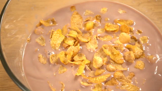 Slow motion of falling corn flakes on wooden background