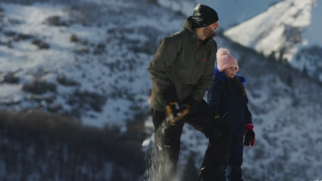 vidéos et rushes de slow motion of family having snowball fight near mountain / south fork, utah, united states - insouciance