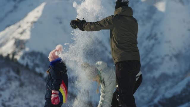 slow motion of family having snowball fight near mountain / south fork, utah, united states - tre quarti video stock e b–roll