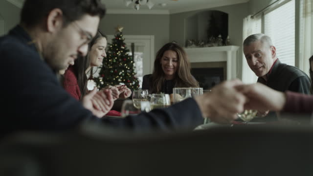 vídeos de stock, filmes e b-roll de slow motion of family holding hands and saying grace at christmas dinner / orem, utah, united states - religião