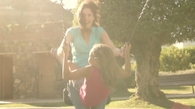 slow motion of family in park, mother and daughter on swing. - altalena video stock e b–roll