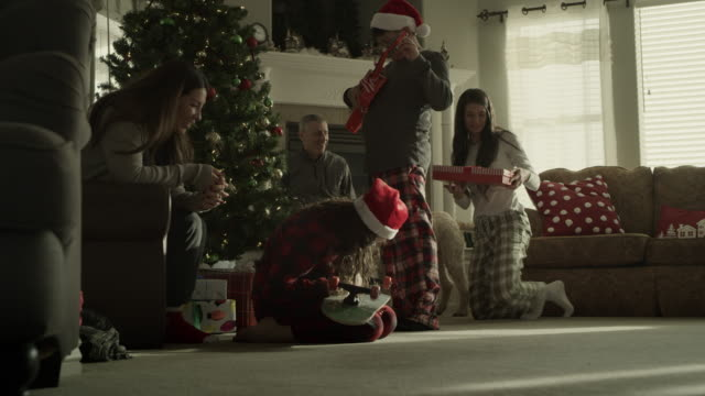 slow motion of family opening gifts on christmas morning / orem, utah, united states - orem bildbanksvideor och videomaterial från bakom kulisserna