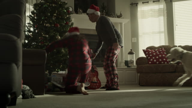 slow motion of family rushing to gifts on christmas morning / orem, utah, united states - orem utah stock videos & royalty-free footage