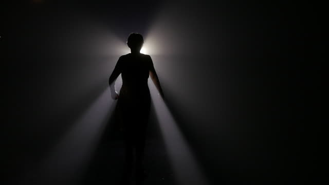 Slow motion of fashion woman walking against light at night