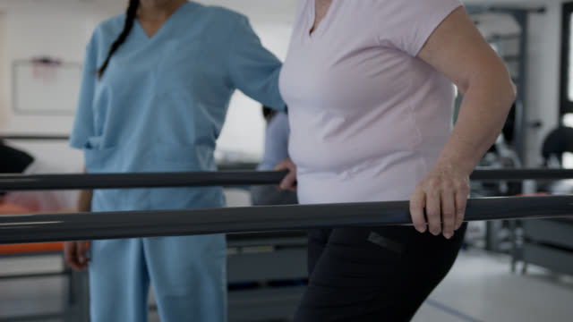 slow motion of female patient walking with the help of parallel bars and female therapists assisting her on each side - medical scrubs stock videos & royalty-free footage