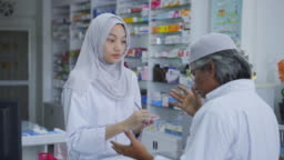 Slow motion of Female pharmacist helping a client with a product,Islam
