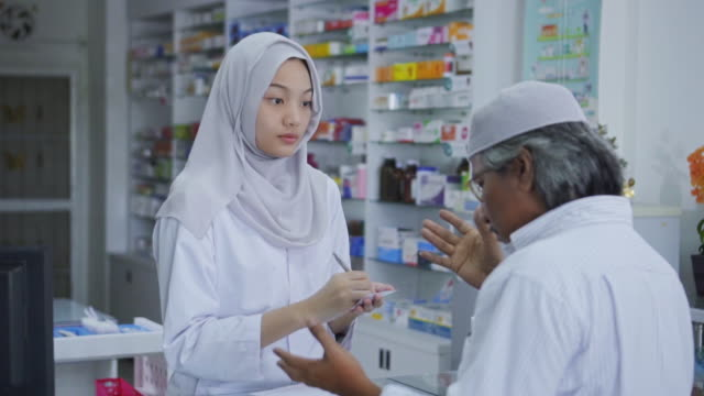 vídeos de stock e filmes b-roll de slow motion of female pharmacist helping a client with a product,islam - cultura tailandesa