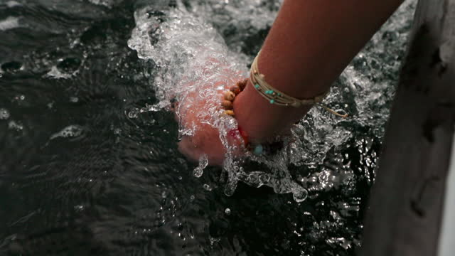 slow motion of female tourist dangling hand in sea waves during vacation - south male atoll, maldives - hängen stock-videos und b-roll-filmmaterial