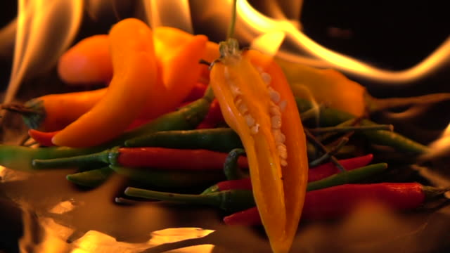 slow motion of fire burning chili on black background - thai food stock videos & royalty-free footage