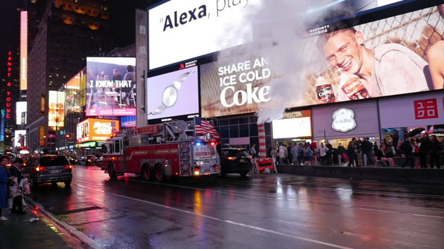 slow motion of fire engine truck with american flag driving in times square, new york city at a rainy night - fire engine stock videos & royalty-free footage