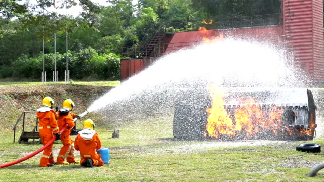slow motion of firemen using fire hose to extinguish a fire of car accident - fire hose stock videos and b-roll footage
