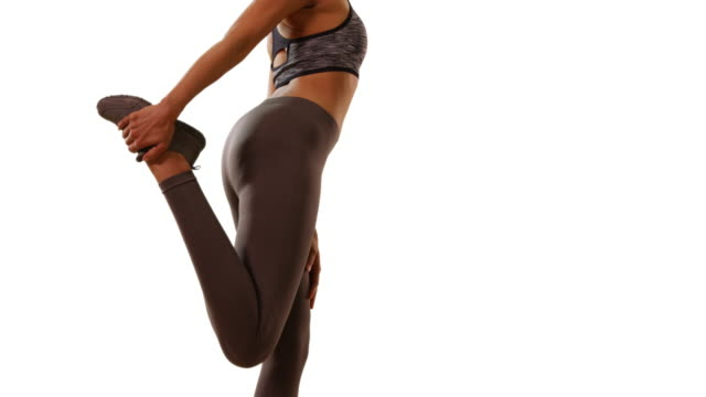 Slow motion of fit black female stretching leg muscles on white background