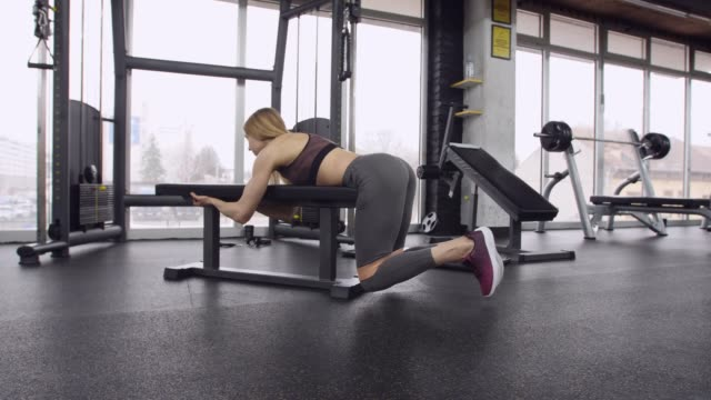 slow motion of fit young woman doing reverse leg curls on a gym bench - lying on front stock videos & royalty-free footage