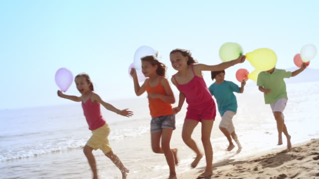Slow motion of five children running by camera on beach holding balloons.
