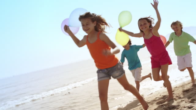 slow motion of five children running by camera on beach holding balloons. - five people stock videos & royalty-free footage