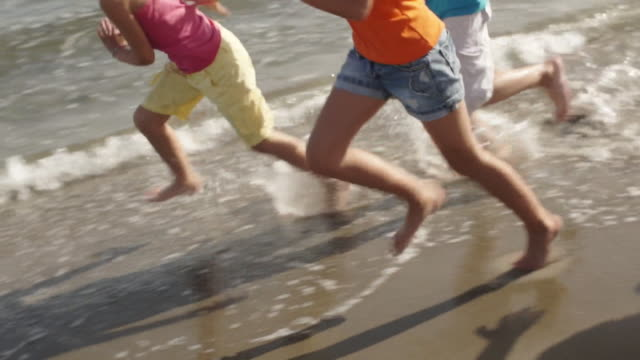 slow motion of five children running on beach. - five people stock videos & royalty-free footage