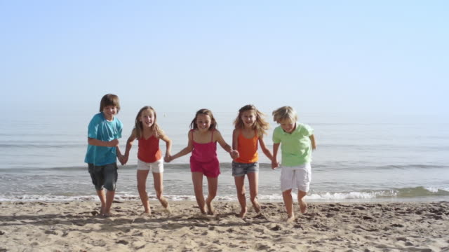 Slow motion of five children running towards camera.