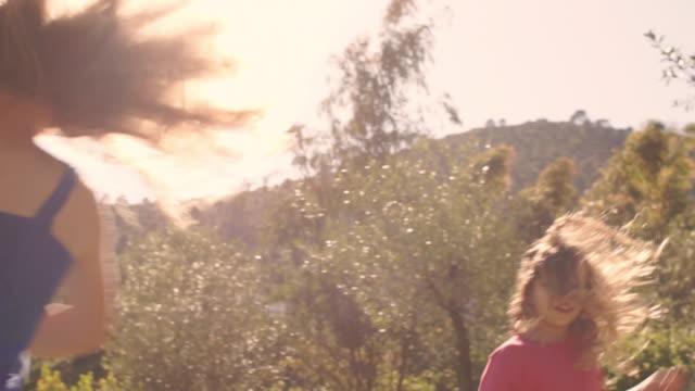 stockvideo's en b-roll-footage met slow motion of five children spinning around in park. - alleen kinderen