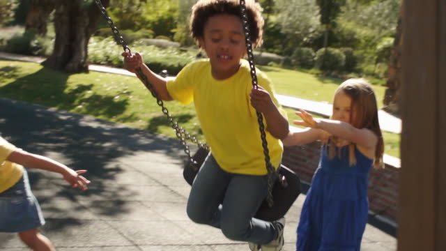 slow motion of four children playing on swings in park. - schaukel stock-videos und b-roll-filmmaterial