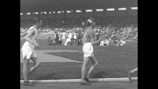 slow motion of four racewalkers with crowd and stadium beyond / sped up footage of walkers / [note film has nitrate deterioration] - 1924 stock videos and b-roll footage