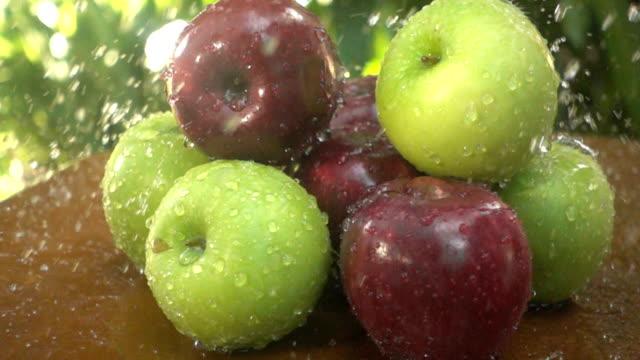 stockvideo's en b-roll-footage met slow motion van verse appelen met water splash - rijp voedselbereiding