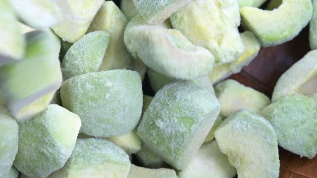slow motion of frozen avocado pieces - frozen stock videos & royalty-free footage