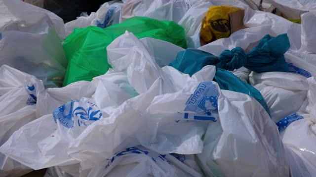 slow motion of garbage bags at beach on sunny day - tel aviv, israel - プラスチック汚染点の映像素材/bロール