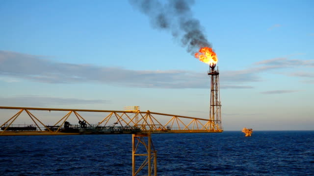slow motion of gas flare burning on the oil and gas offshore platform in the middle of the sea with blue sky for oil and gas industry concept. - petrol stock videos & royalty-free footage