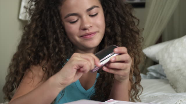 slow motion of girl grabbing her phone to text. - one teenage girl only stock videos & royalty-free footage