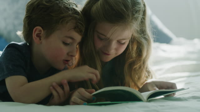 vídeos de stock e filmes b-roll de slow motion of girl reading book to little brother on bed / pleasant grove, utah, united states - irmão