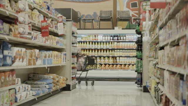 slow motion of girl running in supermarket pushing friend sitting in shopping cart / provo, utah, united states - einkaufswagen stock-videos und b-roll-filmmaterial