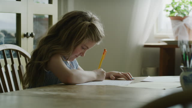 vídeos de stock e filmes b-roll de slow motion of girl sitting at table writing on paper with pen / pleasant grove, utah, united states - criança de escola primária