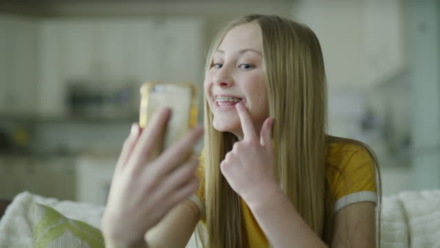 slow motion of girl with braces video chatting on cell phone / highland, utah, united states - brace stock videos and b-roll footage