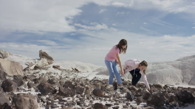 slow motion of girls exploring field of rocks in desert landscape / moore, utah, united states - nur kinder stock-videos und b-roll-filmmaterial