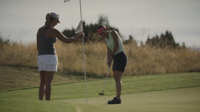slow motion of golfer holding flag for woman successfully putting then high-fiving / cedar hills, utah, united states - golf swing stock videos & royalty-free footage