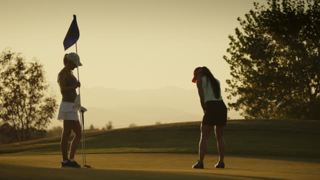 slow motion of golfer putting and missing with friend removing flag / cedar hills, utah, united states - golf swing stock videos & royalty-free footage