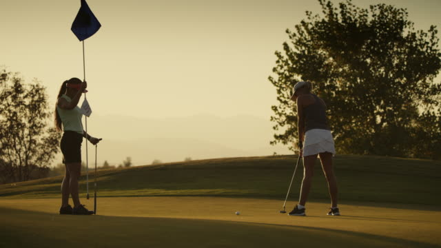 slow motion of golfer putting and missing with friend watching / cedar hills, utah, united states - golf swing women stock videos & royalty-free footage