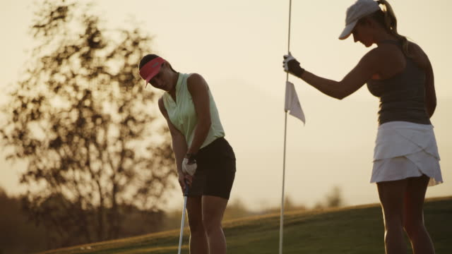 slow motion of golfer putting then high-fiving with friend removing flag at sunset / cedar hills, utah, united states - human limb stock videos & royalty-free footage
