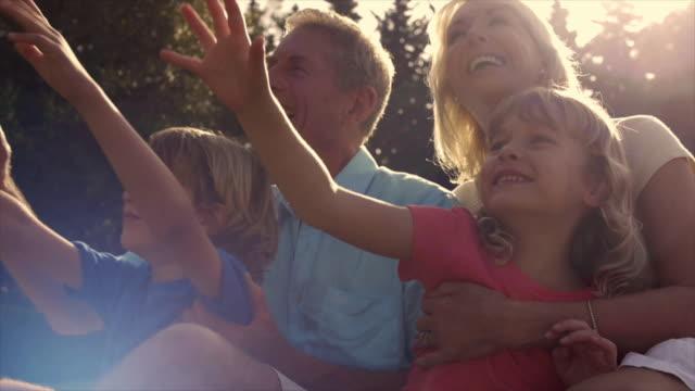 vidéos et rushes de slow motion of grandchildren and grandparents in garden playing with bubbles. - affectionate