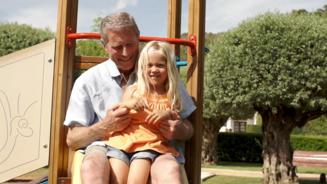 slow motion of grandfather and granddaughter on slide in park. - grandfather stock videos & royalty-free footage