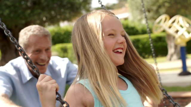 Slow motion of grandfather pushing granddaughter on swing in park.