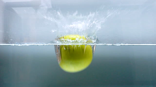 slow motion of green apple drop in the water - apple fruit stock videos and b-roll footage