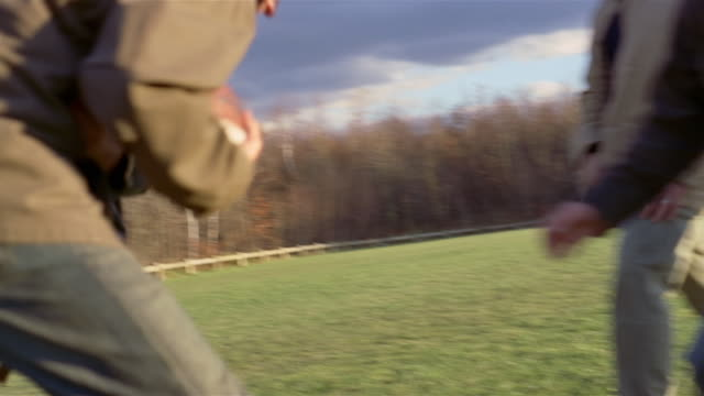 slow motion of group of men playing touch football in field - touch football stock videos & royalty-free footage
