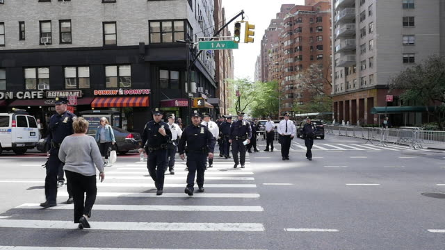 Slow motion of group of NYPD police officier crossing street in New York City